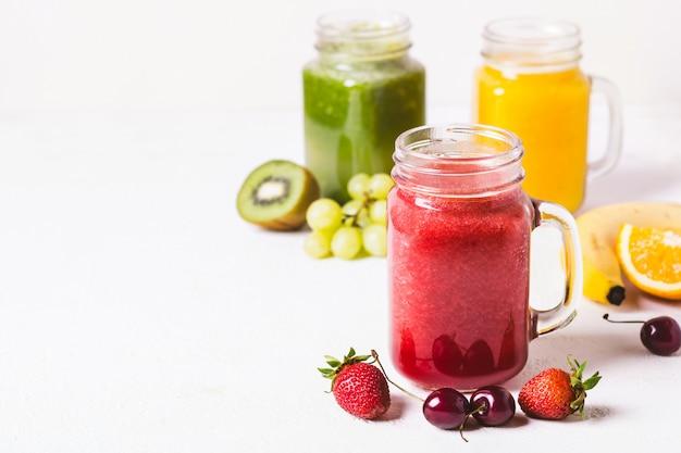 Batido rojo, amarillo y verde en un frasco de vidrio e ingredientes