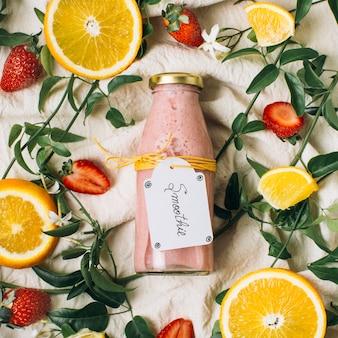 Batido rosa junto a limones y fresas.