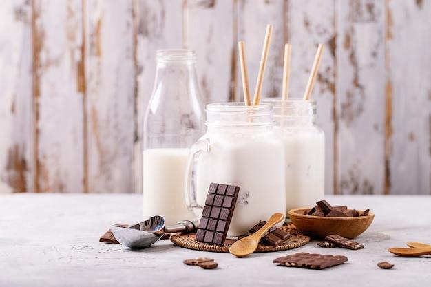 Batido de vainilla servido con chocolate sobre fondo de textura blanca