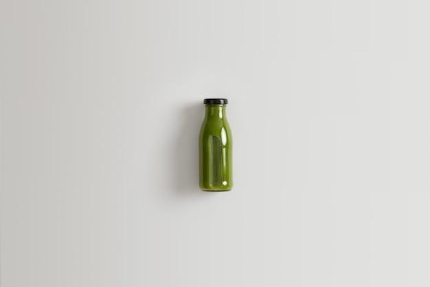 Batido de vegetales verdes saludable preparado a base de espinacas, col rizada y pepinos mezclados con agua para una nutrición adecuada. botella de bebida nutritiva de ingredientes orgánicos sobre fondo blanco.