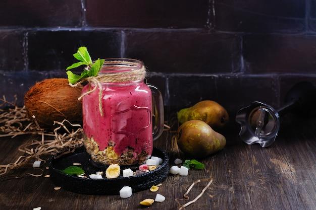 Batido de verano de desintoxicación colorido con bayas rojas, pera, granola y cubos de coco secos