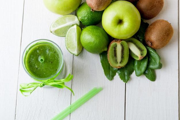 Batido verde cerca de ingredientes para él en madera blanca. manzana, lima, espinacas. desintoxicación bebida saludable. vista superior.