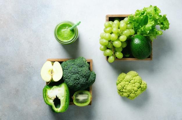 Batido verde en frasco de vidrio con verduras y frutas verdes orgánicas frescas en gris.