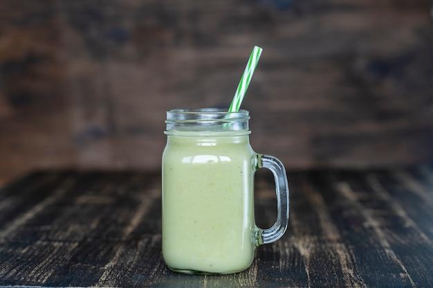 Batido verde fresco de aguacate, plátano y miel en taza de vidrio sobre fondo de madera, de cerca. concepto de alimentación saludable