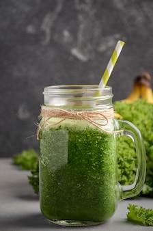 Batido verde fresco con col rizada y plátano en un frasco.