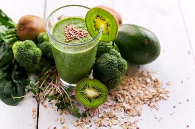 Batido verde fresco y sabroso con ingredientes sobre superficie de madera