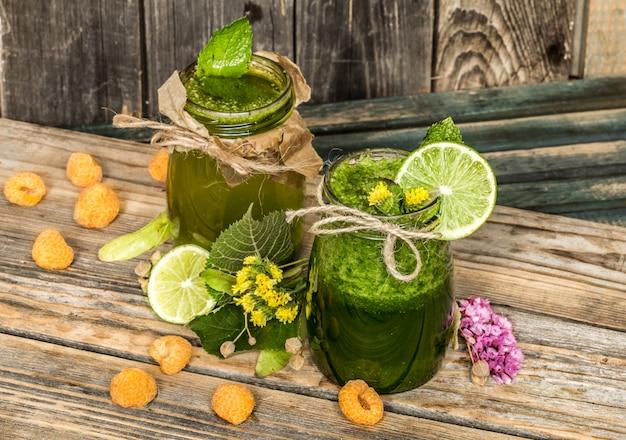 Batido verde en una jarra con lima, kiwi y bayas