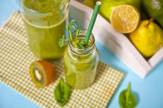 Batido verde mezclado fresco en botellas de vidrio con frutas y verduras