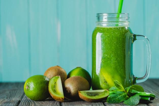 Batido verde mezclado con ingredientes en foco selectivo de mesa de madera.