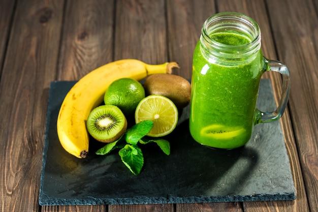 Batido verde mezclado con ingredientes en la mesa de madera de piedra enfoque selectivo