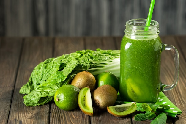Batido verde mezclado con ingredientes en la mesa de madera
