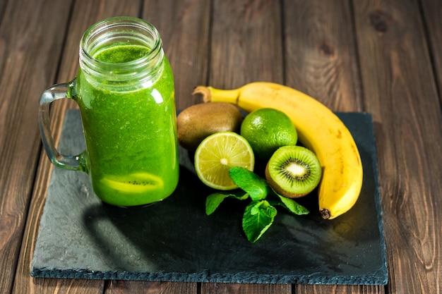 Batido verde mezclado con ingredientes en el tabl de madera de piedra