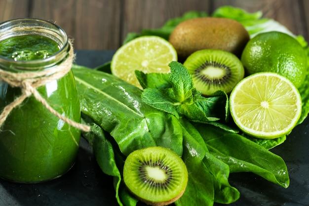 Batido verde mezclado con ingredientes en el tablero de piedra, madera