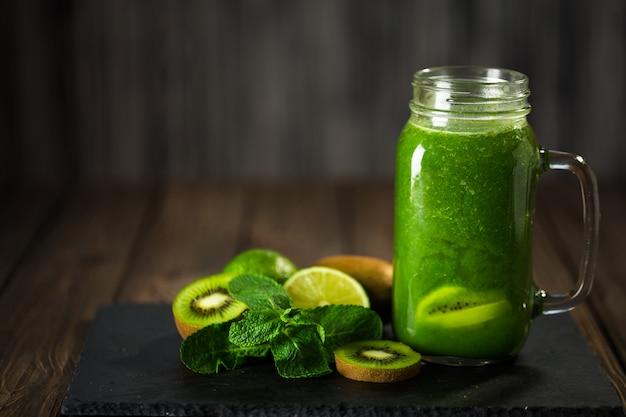 Batido verde mezclado con ingredientes en el tablero de piedra, mesa de madera