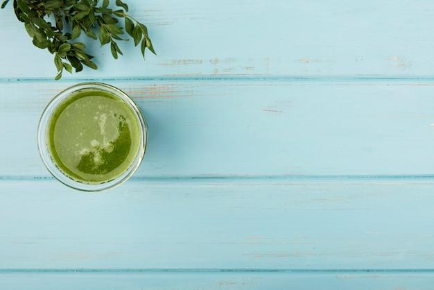 Batido verde natural en vidrio sobre fondo de madera