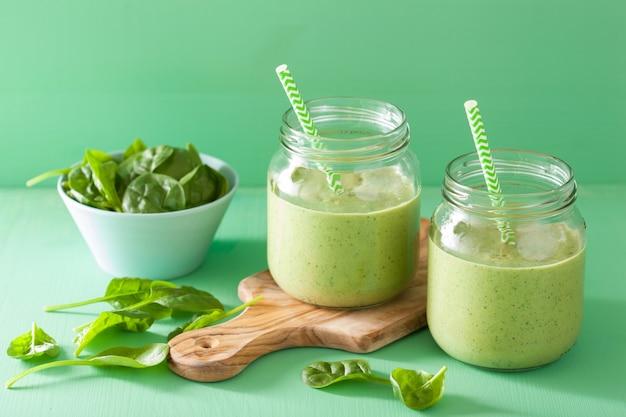 Batido verde saludable con espinacas, mango y plátano en frascos de vidrio