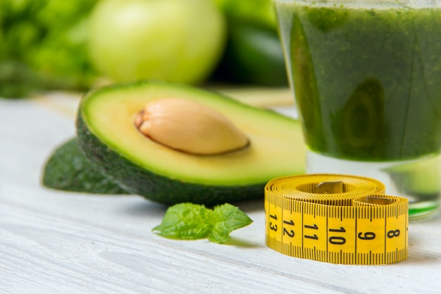 Batido verde saludable con ingredientes en madera blanca