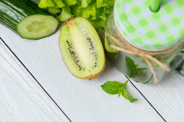 Batido verde saludable con ingredientes sobre fondo blanco de madera