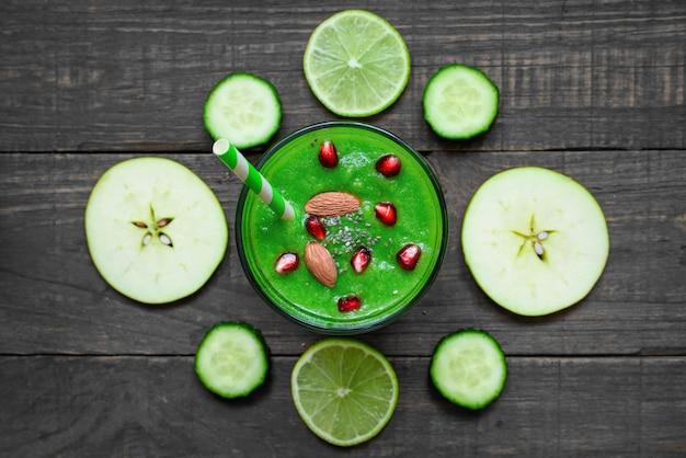 Batido verde saludable en un vaso de semillas de chía, granada y nueces con una pajita sobre mesa de madera rústica. vista superior
