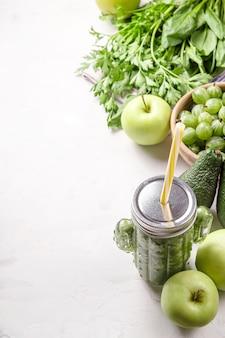 Batido verde en un vaso con forma de cactus entre los ingredientes verdes