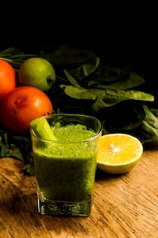 Batido verde en vaso con limón cortado