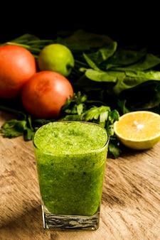 Batido verde en vaso con limón