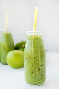 Batido verde vegetariano con verduras y frutas en botellas de vidrio, enfoque selectivo