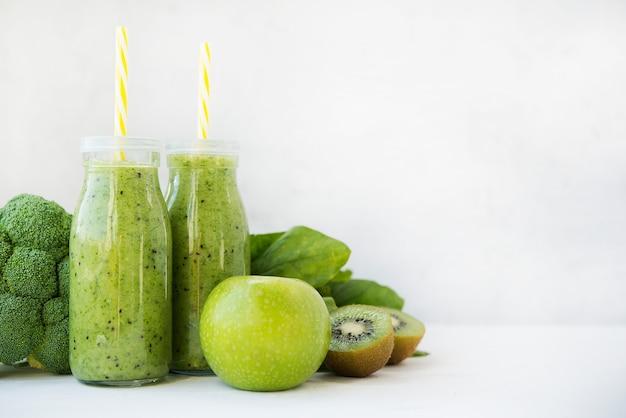 Batido verde vegetariano con verduras y frutas en botellas de vidrio, espacio de copia