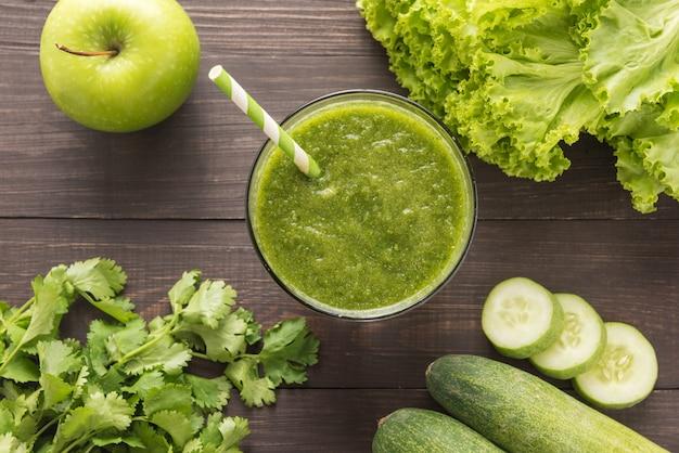 Batido de verduras y frutas verdes saludables en la mesa de madera rústica