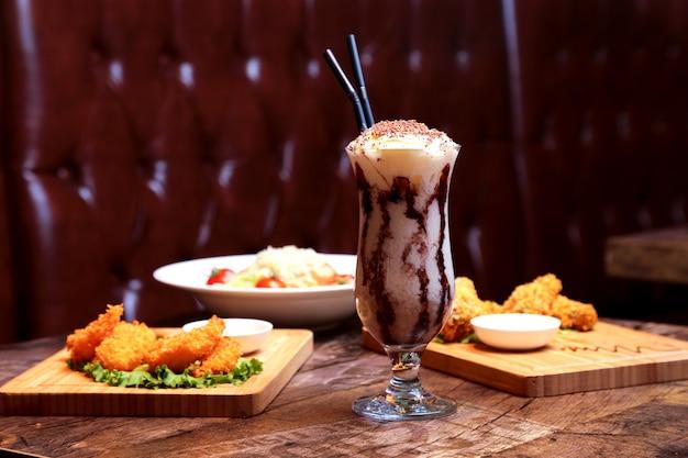 Batido de vista frontal con crema batida y glaseado de chocolate con aperitivos y ensalada en la mesa