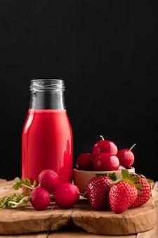 Batido de vista frontal con fresas, cerezas y rábanos
