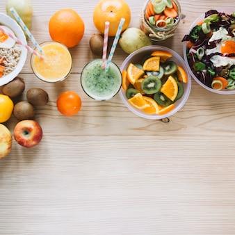 Batido y frutas cerca de platos saludables