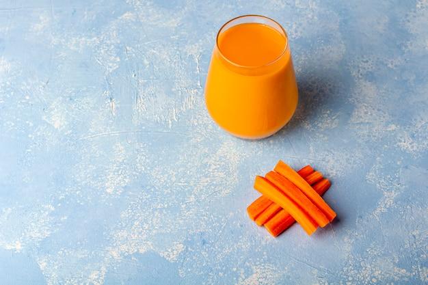 Batido de zanahoria desintoxicante nutritivo. bebida vegetariana orgánica fresca y rodajas de zanahorias. concepto de alimentación saludable nutrición adecuada, concepto de dieta de fitness. jugo de naranja en un vaso.