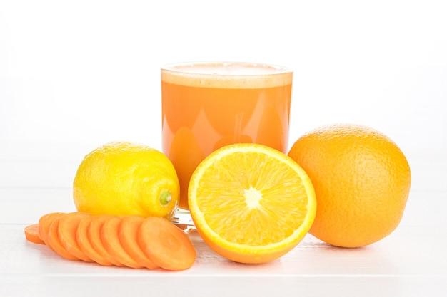 Batido de zanahoria con naranja y limón sobre una mesa de madera blanca.