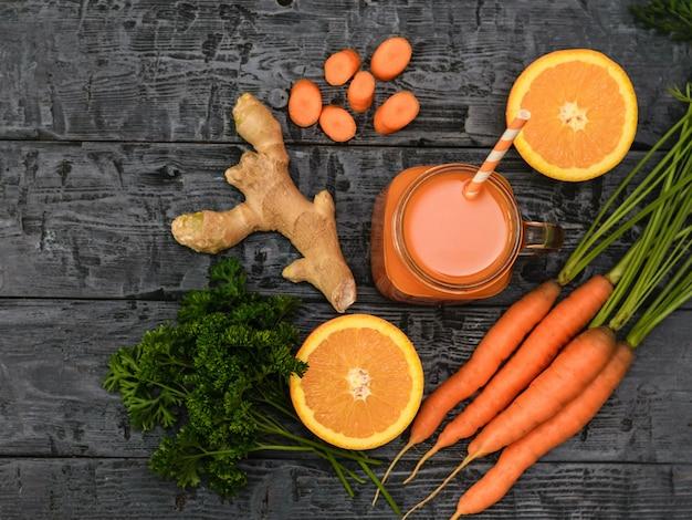 Batido de zanahoria recién hecho, manojo de zanahorias, perejil, naranja y raíz de jengibre sobre una mesa rústica.