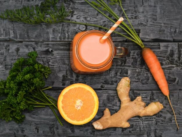 Batido de zanahoria recién hecho, zanahoria, perejil, naranja y raíz de jengibre en una mesa rústica.