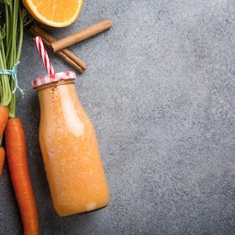 Batido de zanahoria saludable con naranja y canela en botella de vidrio e ingredientes.