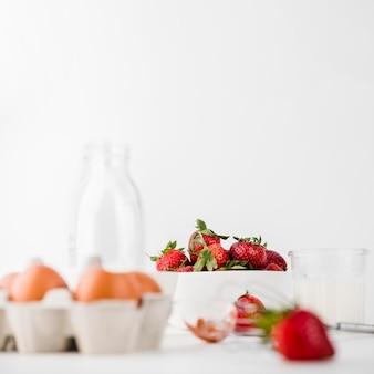 Batidor de primer plano con fresas y huevos
