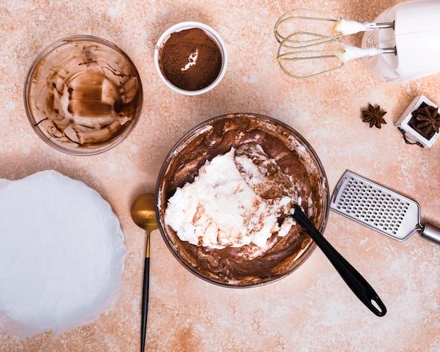Batidora eléctrica; rallador de mano anís estrellado; polvo de cacao y masa de pastel sobre fondo con textura marrón