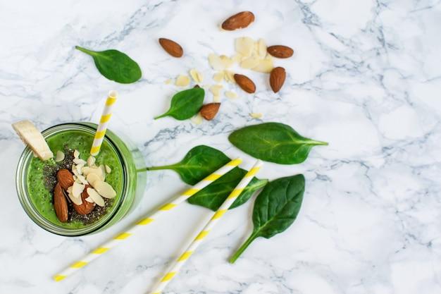Batidos de espinacas verdes en frasco con semillas de chía, nueces almendras, concepto de comida saludable