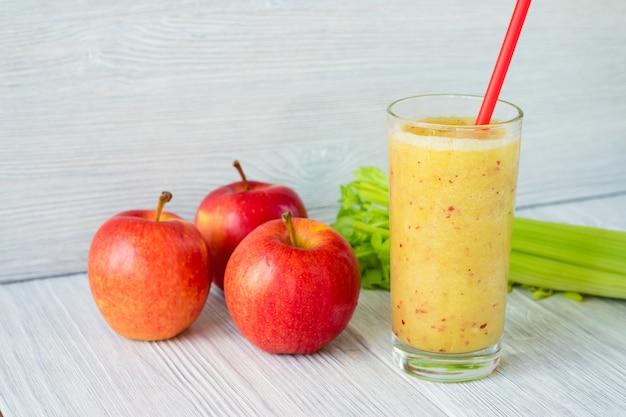 Batidos hechos de manzanas y apio en un vaso con una pajita en una mesa