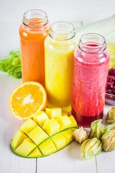 Batidos multicolores en botellas de mango, naranja, plátano, apio, bayas, en una mesa de madera.