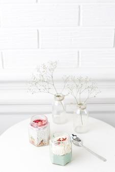 Batidos de tarro de cristal y bebé respira flor en florero sobre mesa blanca