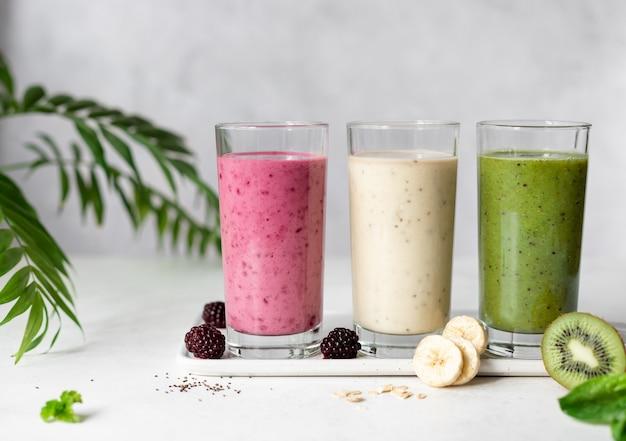 Batidos veganos coloridos con moras, plátano y avena, kiwi y espinacas concepto de comida vegana fondo gris con hojas de palma horizontales, espacio de copia,