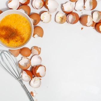 Batir los huevos con un batidor. yemas y proteína de huevo en una taza. corolla batir los huevos. preparación de comida y huevos de gallina. cáscara de huevo sobre una mesa. vista desde arriba.