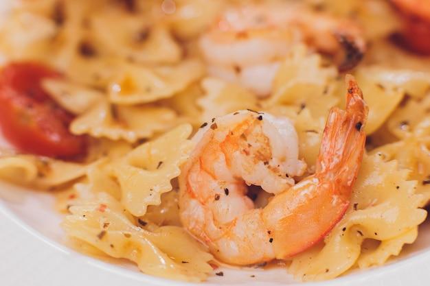 Bavette de pasta con camarones fritos, salsa bechamel, hojas de menta, ajo, tomates, chile en un plato blanco, vista superior, cocina italiana.