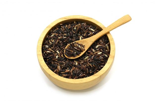 Baya de arroz jazmín aislado en un tazón de madera y cuchara