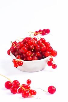 Baya de la grosella roja de la fruta del verano en taza de cerámica en el fondo blanco con el espacio de la copia