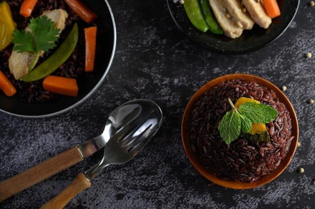 Bayas de arroz morado cocidas con pechuga de pollo a la parrilla calabaza hojas de zanahoria las hojas de menta en el plato y la cuchara, tenedor, comida limpia.
