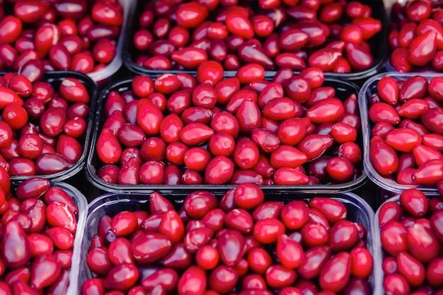Bayas de cornejo rojo en caja de plástico transparente contenedor en los estantes de una calle. cosecha de cornejo a la venta. moras frecas.